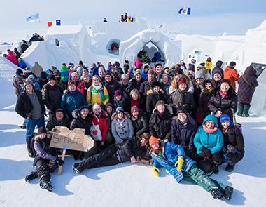 Le Spiritus Chamber Choir, accompagné de la compositrice Carmen Braden et des membres de l'ensemble à cordes, prennent une photo de groupe au célèbre Snow Palace de Yellowknife, T.‑N.‑O.