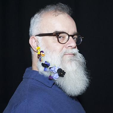 Rodney Sharman, compositeur pose avec des fleurs dans sa barbe.