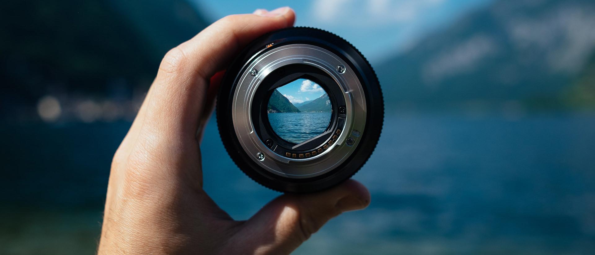 La main d'une personne tenant une lentille de caméra au-dessus d'un lac de montagne