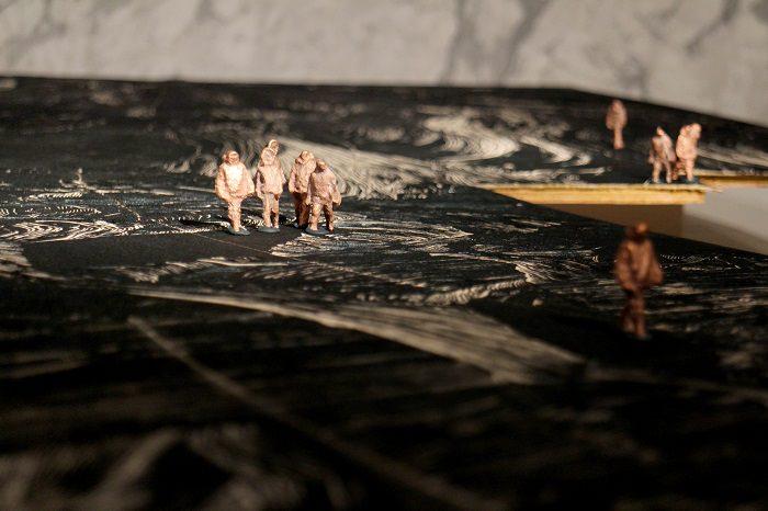 Neuf petites figurines de cuivre représentant des jeunes de Kinngait sont placées sur une surface de bois coupé; certaines d'entre elles sont regroupées, d'autres sont dispersées.