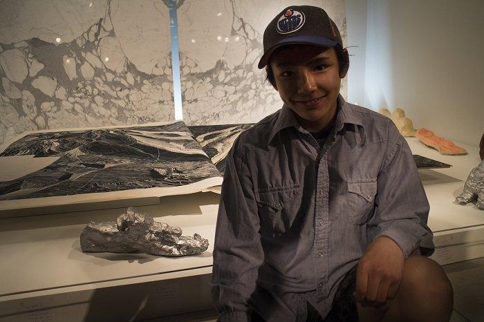 Un jeune homme nommé Lachaolasie est assis devant des œuvres d'art au Musée des beaux-arts de l'Ontario, y compris sa sculpture d'une motoneige.